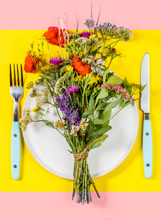 Flat lay of wild flower bouquet on white plate. Clean eating, paleo, biohacking, herbal medicine concept Stock Photo