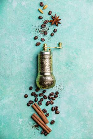 Top view of  vintage manual coffee grinder, coffee beans and spices, space for text, blue Banco de Imagens