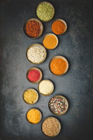Various bowls of spices over dark