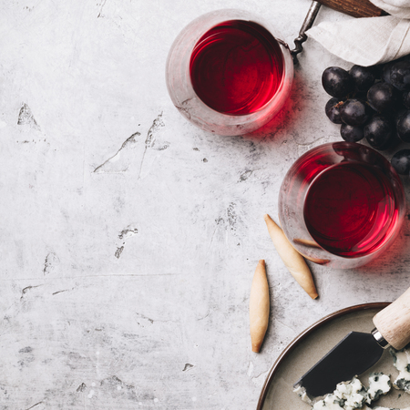 Glasses of red wine, cheese and grapes on rustic concrete background, copyspace, flat lay