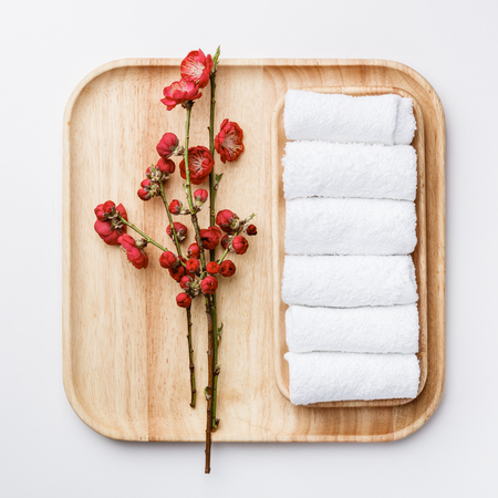 Spa treatment concept, flat lay composition with towels and spring flowers on white background