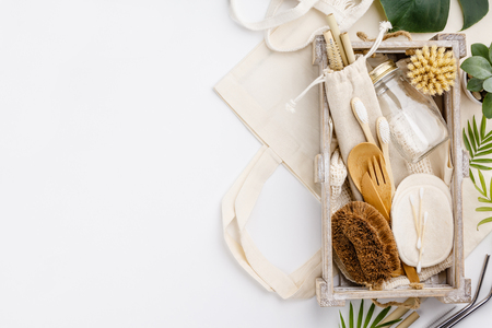Natural color eco bags, reusable metal and bamboo straws, glass jars, wooden knifes and forks, zero waste cleaning and beauty products, flat lay