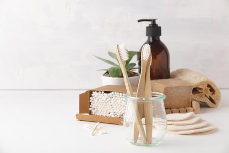 Zero odpadów, recykling, koncepcja zrównoważonego stylu życia. Ekologiczne akcesoria łazienkowe: szczoteczki do zębów, bawełniane płatki do demakijażu wielokrotnego użytku, płyn do demakijażu w szklanym pojemniku, pędzle naturalne, mydło ręcznie robione, bambusowe patyczki do uszu