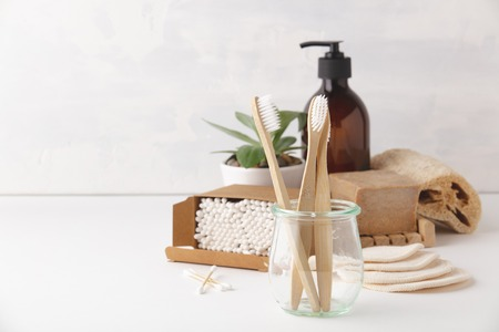 Zero waste, Recycling, Sustainable lifestyle concept. Eco-friendly bathroom accessories: toothbrushes, reusable cotton make up removal pads, make up remover in a glass container, natural brushes, hand 스톡 콘텐츠