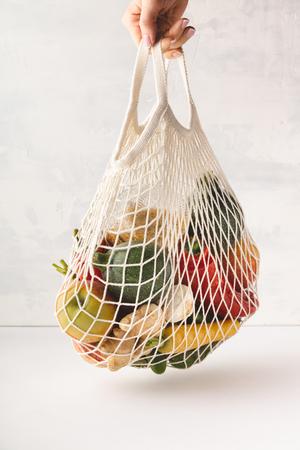 Kobieca ręka trzyma bawełnianą torbę mieszanych owoców i warzyw. Zero odpadów, recykling, koncepcja zrównoważonego stylu życia