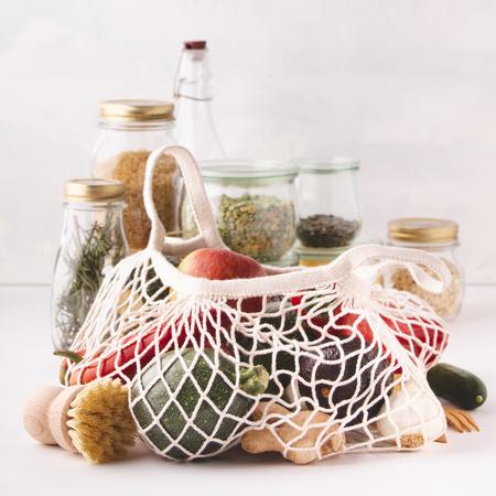 Frutas y verduras en bolsas de algodón reutilizables y frascos de vidrio con pasta, lentejas, frijoles, arroz, hierbas secas. Cero residuos, reciclaje, concepto de estilo de vida sostenible Foto de archivo