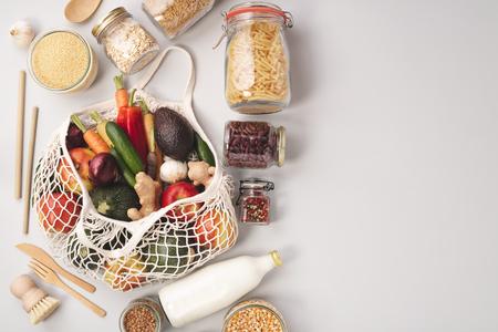 Rifiuti zero concetto. Sacchetti ecologici con frutta e verdura, vasetti di vetro con fagioli, lenticchie, pasta. Shopping ecologico, piatto