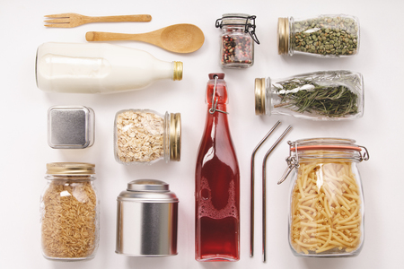 Zero waste home style. Glass and metal jars with beans, pasta, lentils, milk, juce. Metal straws and bamboo fork and spoon. Flat lay