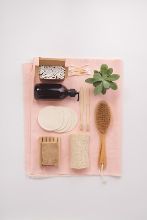Zero waste, Recycling, Sustainable lifestyle concept. Eco-friendly bathroom accessories: toothbrushes, reusable cotton make up removal pads, make up remover in a glass container, natural brush, bamboo ear sticks, olive oil soap. Flat lay