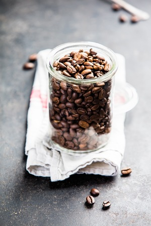 Coffee composition on dark background. Coffee beans in glass jar