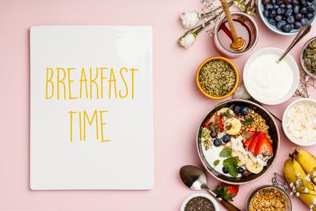 Gesundes Frühstücksset. Hafergranola mit frischen Beeren, Banane, Joghurt, Ahornsirup, Samen und Minzblättern mit Tasse Kaffee auf rosa Hintergrund, flache Lage, Draufsicht