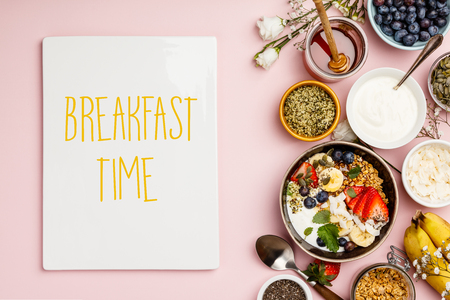 Healthy breakfast set. Oat granola with fresh berries, banana, yogurt, maple syrup, seeds and mint leaves  with cup of coffee on pink background, flat lay, top view
