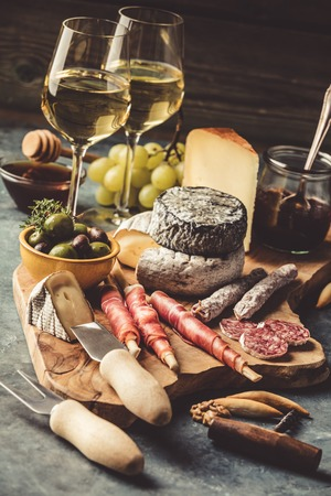 White wine with charcuterie assortment on the stone Фото со стока