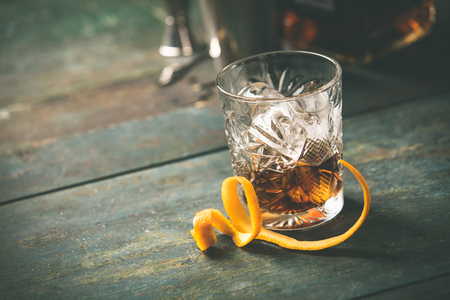 Alcoholic cocktail  with orange peel and ice on wooden table
