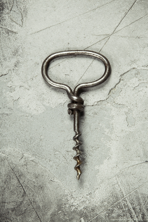 Top view of an old cork screw on gray concrete background with space for text