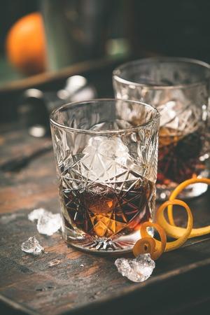 Alkoholischer Cocktail mit Orangenschale und Eis auf Holztisch