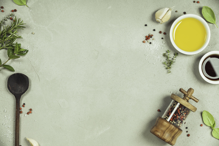 Olive oil, balsamic vinegar, pepper and herbs on concrete background - cooking ingredients -- top view - space for text. Healthy food vegan or diet nutrition concept. Stock Photo