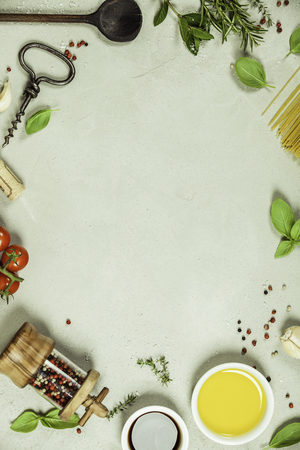 Olive oil, balsamic vinegar, salt, pepper, herbs, pasta, tomatoes on concrete background - cooking ingredients background -- top view - space for text. Healthy food, vegetarian or italian food concept. Stock Photo