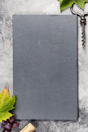 Top view of a blank chalk board for a wine list or menu with an old cork screw and grape leaf on gray concrete background with space for text.  A vertical design template for a tasting invitation or r 스톡 콘텐츠