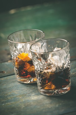 Alcoholic cocktail  with orange peel and ice on wooden table Imagens - 122676725