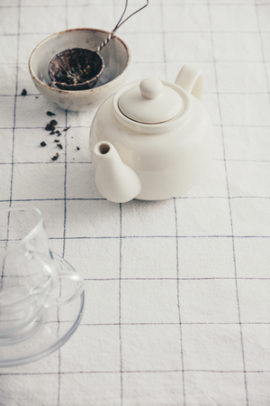 White teapot, cups and strainer on the checkered table cloth