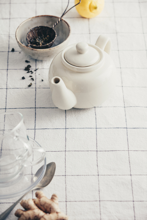 White teapot, cups and strainer on the checkered table cloth Standard-Bild - 123182949