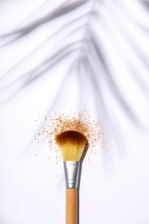 Makeup brush and face powder on a white background