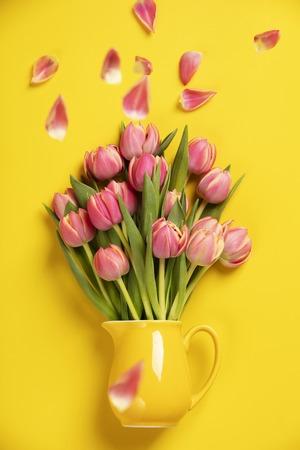 Ta kobieca, kwiatowa fotografia przedstawia ładne świeże różowe tulipany w dzbanku na żółtym tle. Łatwe do pobrania, to zdjęcie stockowe jest idealne do wykorzystania w Twojej witrynie internetowej, marketingu cyfrowym w mediach społecznościowych.