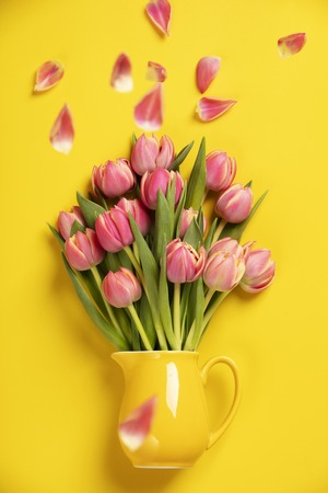 This feminine, floral stock photograph features pretty Fresh pink tulips in a jug on yellow background. Easily downloaded, this stock photo is perfect to use with your website, social media digital ma