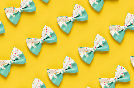 Colorful hair bow pattern on pastel blue background, flat lay, top view Standard-Bild - 123837824