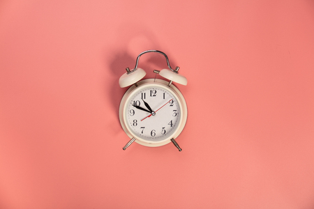 White alarm clock on pink background - flat lay