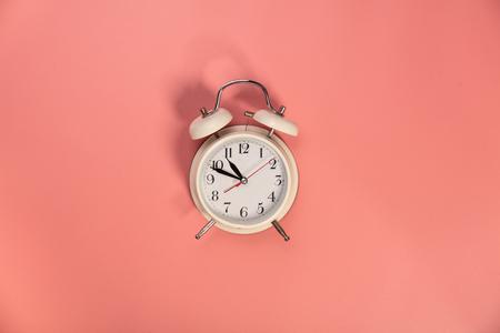 Witte wekker op roze achtergrond - plat lag