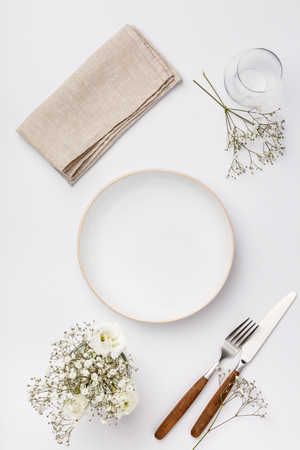 Empty white plate and cutlery on a napkin Standard-Bild - 124680767