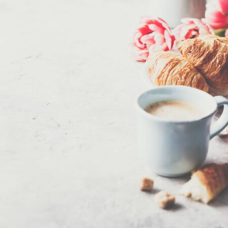 Morning coffee, croissants and spring tulips on light grey background Standard-Bild - 124959310