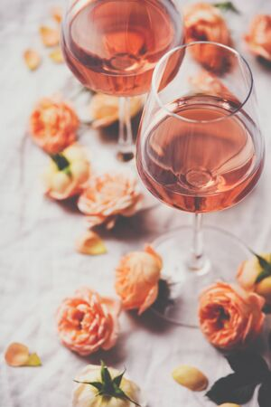 Rose wine and roses on white background, top view 版權商用圖片