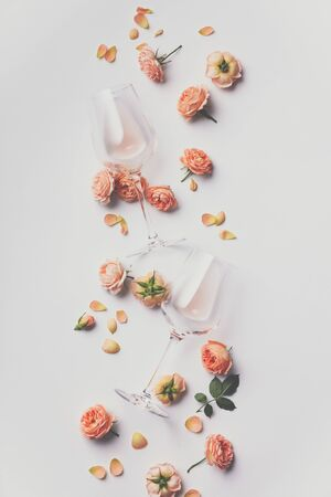 Rose wine and roses on white background, flat lay Foto de archivo