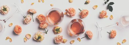 Rose wine and roses on white background, flat lay Stock Photo