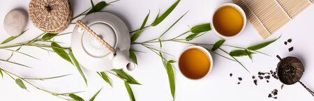 Asiatisches Essen Hintergrundset mit grünem Tee, Tassen und Teekanne mit Bambuszweigen