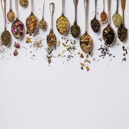 Assortment of dry tea in vintage spoons. Tea types backgound, flat lay, space for text Фото со стока