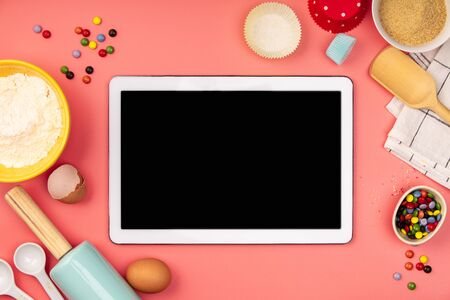 Baking background frame. Ingredients, kitchen items for baking and empty tablet. Kitchen utensils, flour, eggs, sugar. Text space, top view.