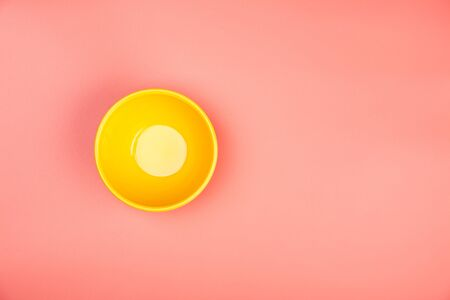 Yellow bowl on pastel pink background, flat lay, copy space