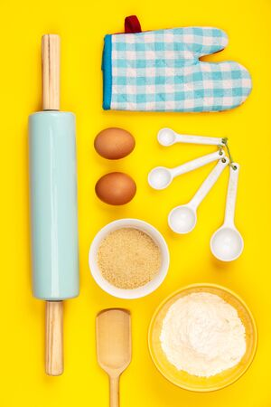 Baking or cooking ingredients on yellow background, flat lay. Ingredients, kitchen items for baking. Kitchen utensils, flour, eggs, sugar. Text space, top view. Zdjęcie Seryjne