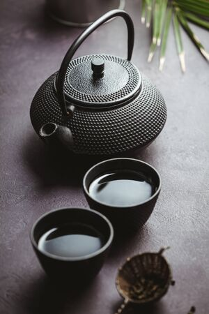 Traditional Asian tea ceremony arrangement. Iron teapot, cups, dried green tea leaves, ginger and tropical leaves over purple concrete background, top view, copy space Stockfoto