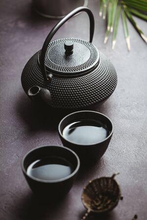 Traditionelle asiatische Teezeremonie. Eisenteekanne, Tassen, getrocknete grüne Teeblätter, Ingwer und tropische Blätter über violettem Betonhintergrund, Draufsicht, Kopierraum