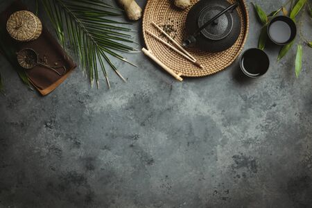 Traditional Asian tea ceremony arrangement. Iron teapot, cups, dried green tea leaves, ginger and tropical leaves over dark concrete background, flat lay, copy space Zdjęcie Seryjne
