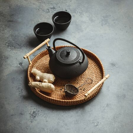 Traditional Asian tea ceremony arrangement. Iron teapot, cups, dried green tea leaves, ginger and tropical leaves over dark concrete background,  copy space