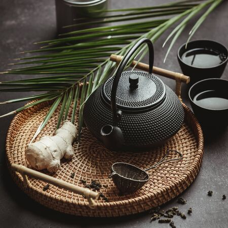 Traditional Asian tea ceremony arrangement. Iron teapot, cups, dried green tea leaves, ginger and tropical leaves over  concrete background Zdjęcie Seryjne