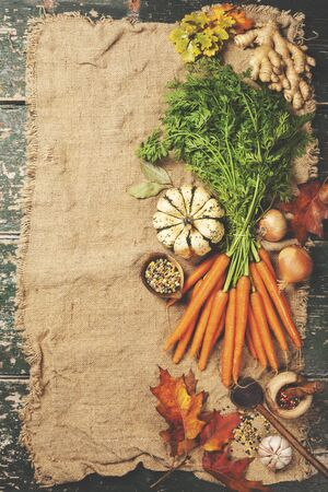 Healthy food cooking background. Vegetable ingredients. Fresh garden carrots, onions, pumpkins, ginger and spices on rustic wooden background, top view, copy space