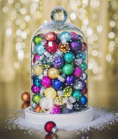Christmas decoration on abstract gold background. Christmas balls inside the Christmas snow globe. Stockfoto