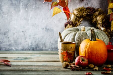 Autumn background with cup of tea or coffee, pumpkins, pumpkin pie spices and leaves on wooden tabel against old rust condition vintage wall, space for text 版權商用圖片 - 128235459